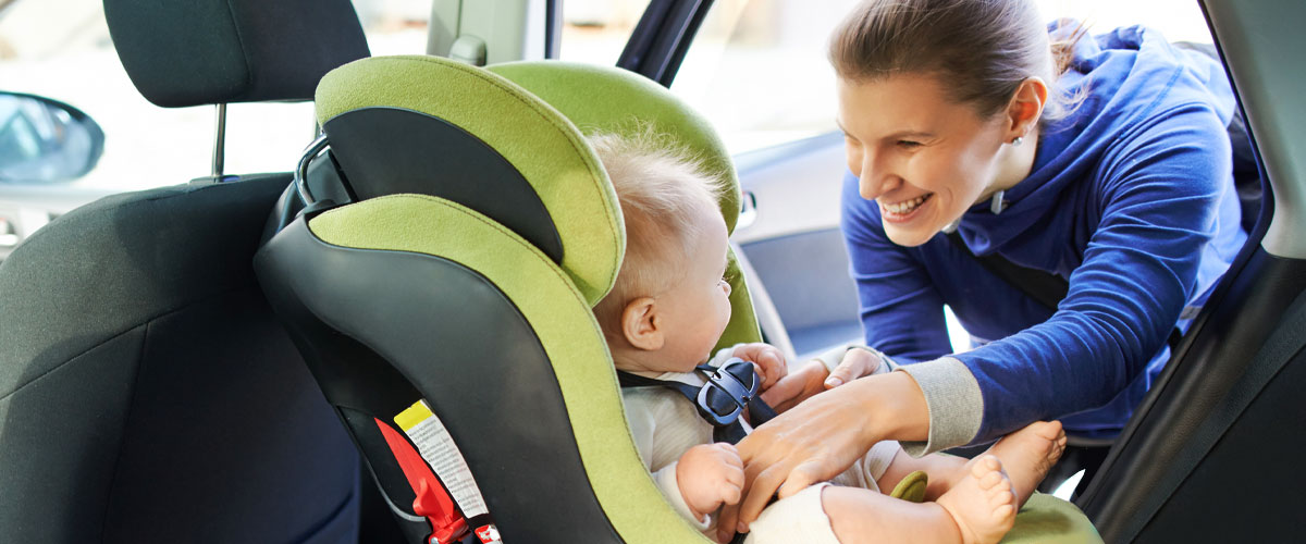 Adult strapping baby into rear facing car seat.