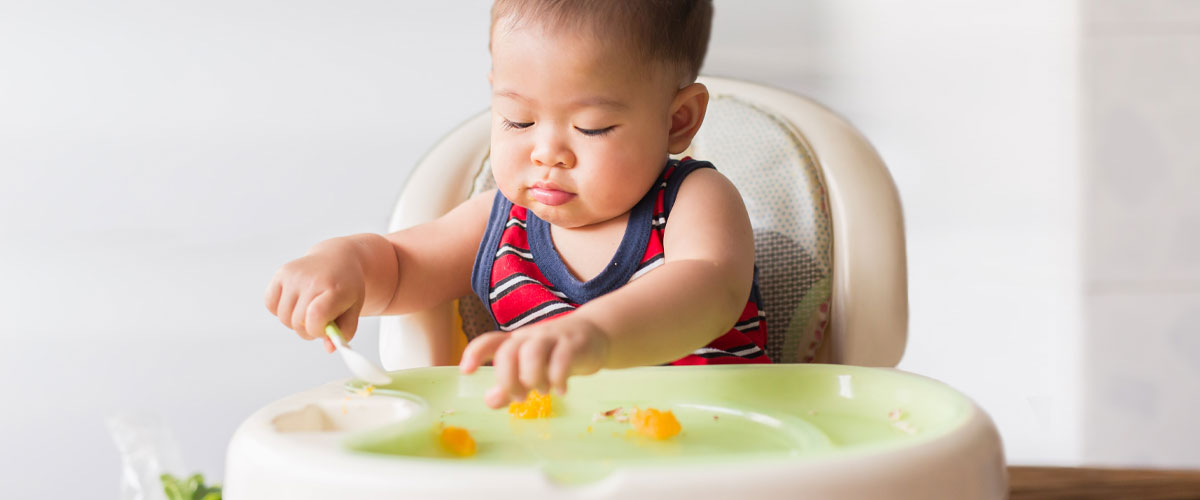 Baby in high chair holding a spoon and reaching for food.