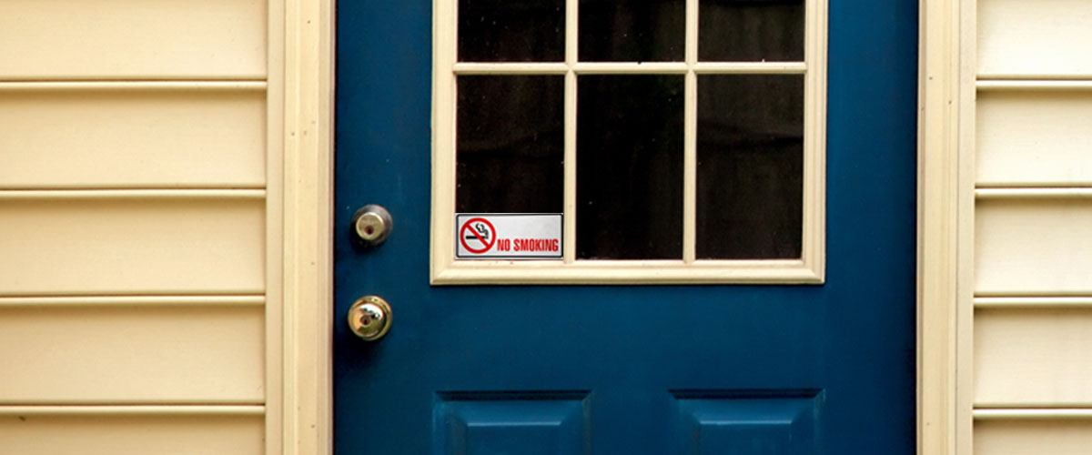 House door with no smoking sign in the window.